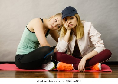 Two attractive women wearing sports clothes sitting on exercise mat being bored or tired after hard workout.