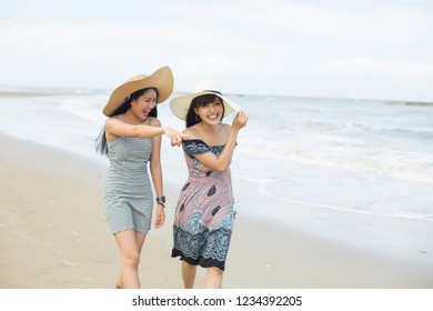 two attractive young asian women walking on the tropical beach with happiness