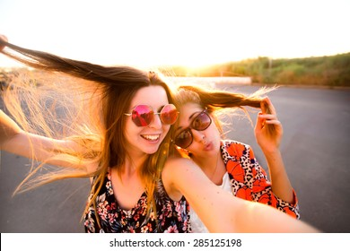 Two attractive young girl friends standing together and posing on camera.Brunette having fun and showing sign with her hand.photography at sunset.two women taking selfie with mobile phone with fisheye