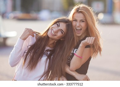 Two attractive young girl friends standing together and posing on camera.Brunette having fun and showing sign with her hand.photography at sunset