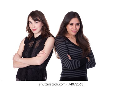 Two attractive young ladies, arms folded, standing close to each other