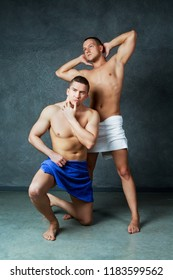 two attractive young men with towels on their hips after taking a shower, against studio background