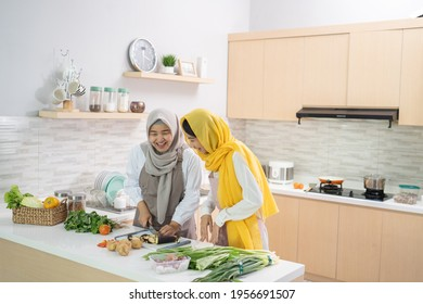 two attractive young muslim woman preparing iftar dinner together. Ramadan and eid mubarak cooking in the kitchen