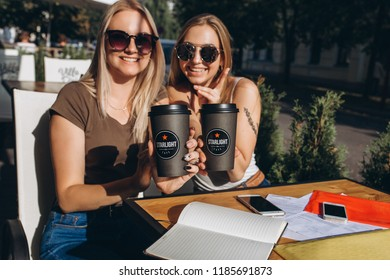 Two attractive young positive nice girls drink coffee in street cafe in european city. August 2018, Prague