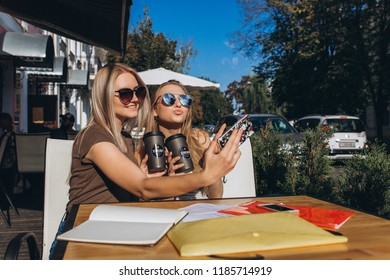 Two attractive young positive nice girls do selfie with cup of coffee in street cafe in european city. August 2018, Prague