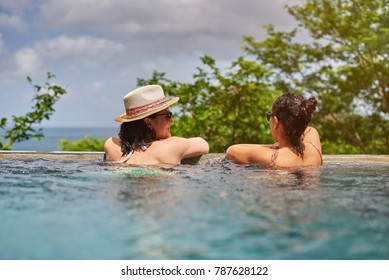 Two attractive young woman in pool on tropics background