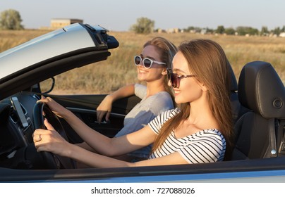 Two attractive young women in a cabriolet car