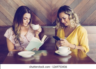 Two attractive young women drinking coffee and resting in cafe. Smiling girl texting when her friend reading book at table in coffeeshop. Pastime concept