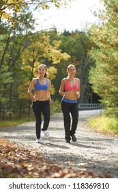 Two attractive young women exercising in rural setting with autumn colors in background.