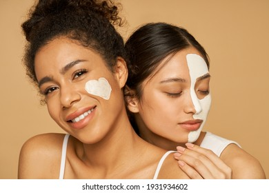 Two attractive young women with facial masks on posing isolated over beige background