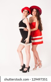 Two attractive young women with hats at white background