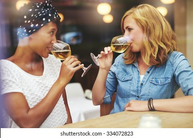 Two attractive young women meeting up in a pub for a glass of white wine sitting at a counter smiling at each other as they sip their glasses