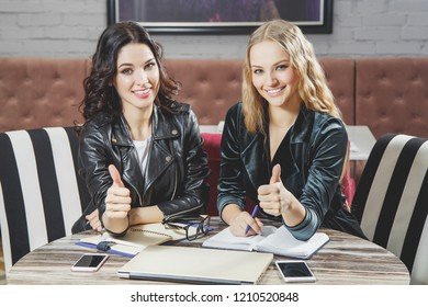Two attractive young women showing thumb up. Business meeting