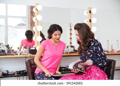Two attractive young women using tablet and reading magazine in beauty salon