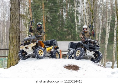 Two ATV riders with paintball guns sitting on quad bikes