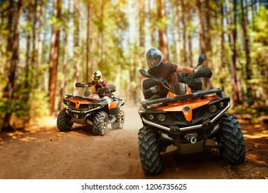 Two atv riders, speed race in forest, front view