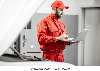 Two auto mechanics in red uniform doing engine diagnostics with computer in the car service
