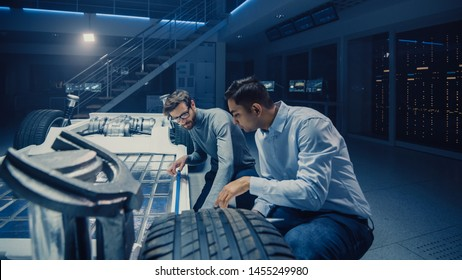 Two Automotive Engineers Working on Electric Car Chassis Platform, Taking Measures, working with 3D CAD Software, Analysing Efficiency. Vehicle Frame with Wheels, Engine and Battery.