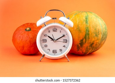 Two autumn pumpkins and white alarm clock at Halloween holiday on orange background.