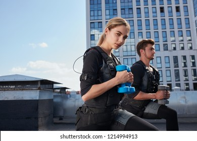 two awesome young people are doing exercises with ems suits on the roof of a modern building. close up side view photo