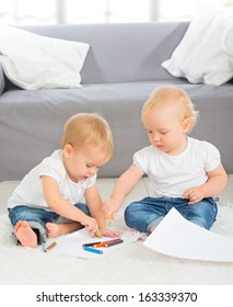two babies draw with crayons at home sitting on the floor