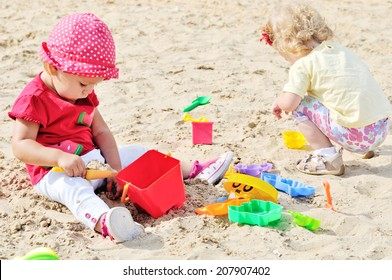 two babies playing toys in sand