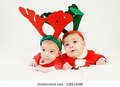 two baby boys lying down on their bellies looking up  wearing red Christmas costume and deer horns isolated on White background