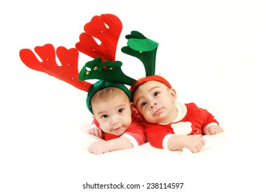 two baby boys lying down on their bellies looking up at the camera wearing red Christmas costume and deer horns isolated on White background
