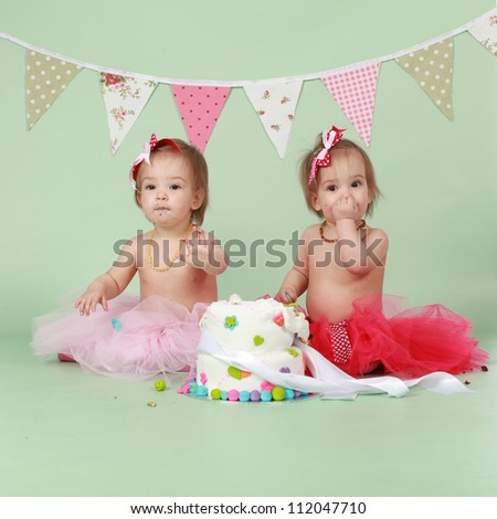 Two Baby Girl Identical Twin Sisters Sitting On Green Seamless Background Behind Decorated Birthday Cake Wearing
