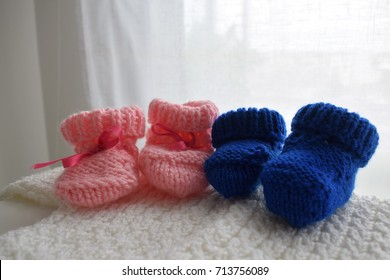 Two baby wool shoes, one pink and one blue. They can be use for twins. They are above a handmade woven white pullover, also for a newborn.