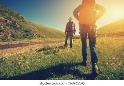 two backpacking women hiking in riverside mountains