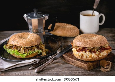 Two Bagels with stew beef, fresh salad, bacon, scrambled eggs and fried onion served on vintage metal tray and wooden chopping board with cup of coffee and coffee pot over wooden table.