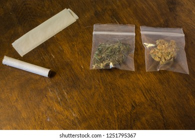 Two bags of marijuana and a joint and rolling paper on a table.