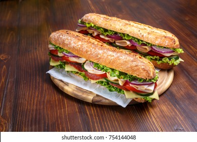 Two baguette sandwiches with salami, turkey breast, cheese, lettuce, tomatoes and onion on a cutting board. Subway sandwiches on a dark background.