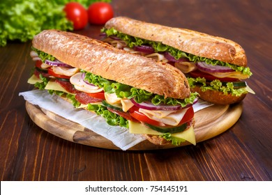 Two baguette sandwiches with salami, turkey breast, cheese, lettuce, tomatoes and onion on a cutting board. Long subway sandwiches on a dark background.