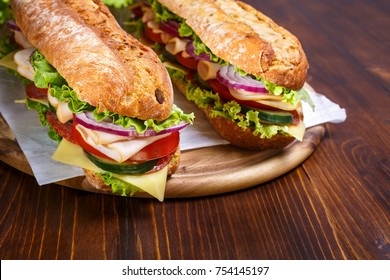 Two baguette sandwiches with salami, turkey breast, cheese, lettuce, tomatoes and onion on a cutting board