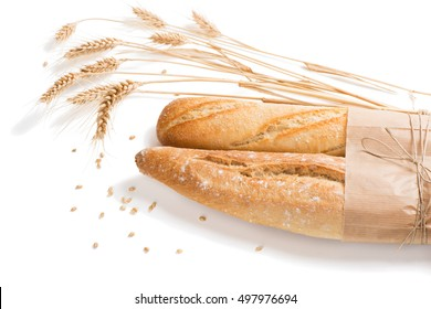 Two baguettes bread with wheat ears isolated over white background.