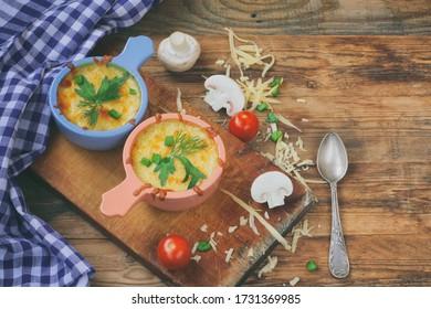 dos julianas al horno con paladines, cebollas y queso sobre una mesa de madera, toalla de cuadros azules, vista superior