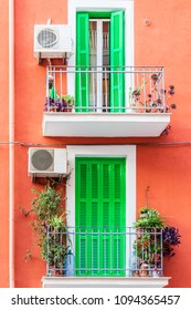 Two balconies and from the outside plants and windows of green color.