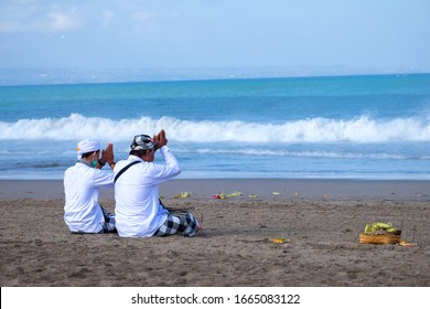 Two balinese are praying in the beach