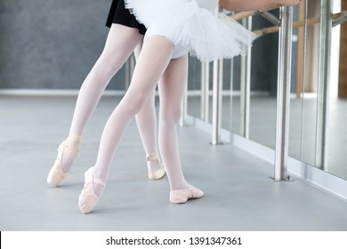 Two ballerinas child girl and woman in ballet pointe shoes. Little kid and adult teacher are studying choreographic position for legs in front of mirror in classical dance school. Close up.