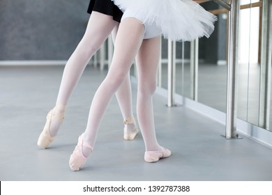 Two ballerinas child girl and woman in ballet pointe shoes. Little kid and adult teacher are studying choreographic position for legs in classical dance school. Practicing for children. Close up.