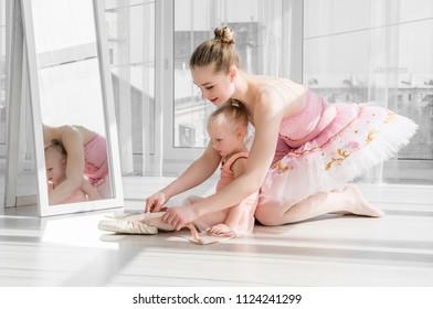 Two ballerinas sitting on the split