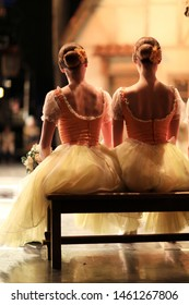 Two ballet dancers from the Corps de Ballet are sitting on a bench backstage.