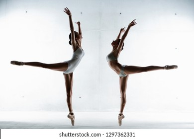 Two ballet dancers in powerful pose lifting legs facing each other, competing synchronised, mirror figures silhouettes on stage. Conceptual teamwork strength coordination, beauty body form fitness.