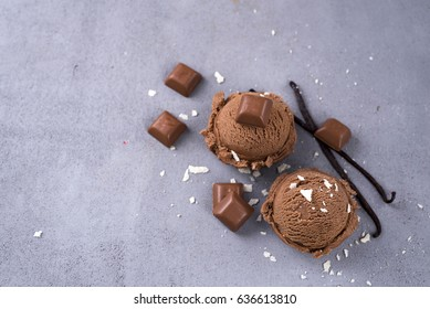 Two balls of chocolate ice cream with a vanilla stick and chunks of chocolate on a dark background