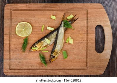 Two baltic herrings cold smoked with dill, green onions and lime on a wooden cutting board. Two aromatic baltic herrings smoked until golden. Close up