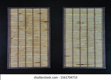 two bamboo mats on wooden table - Shutterstock ID 1561704715
