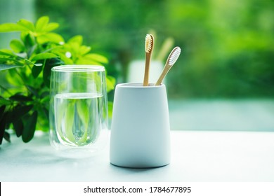 Two bamboo toothbrushes in a cup and glass with water