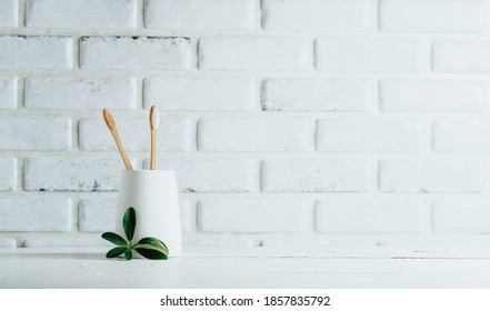 Two bamboo toothbrushes in a glass, minimalistic style in the bathroom, dental care